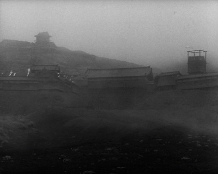 The film opens with a blasted, barren landscape punctuated by a solitary monument marked 'The site of Cobweb Castle'. The swirling fog thickens and then parts again to reveal the once-great castle as it was at the beginning of the events depicted