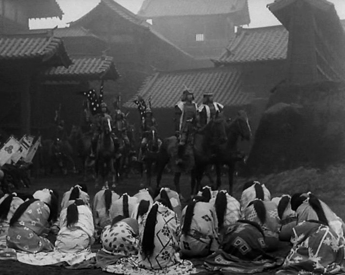 A funereal atmosphere pervades the courtyard of Cobweb Castle as Washizu rides among the inhabitants mourning the death of its ruler, Lord Tsuzuki, whom Washizu's wife Asaji has persuaded him to murder