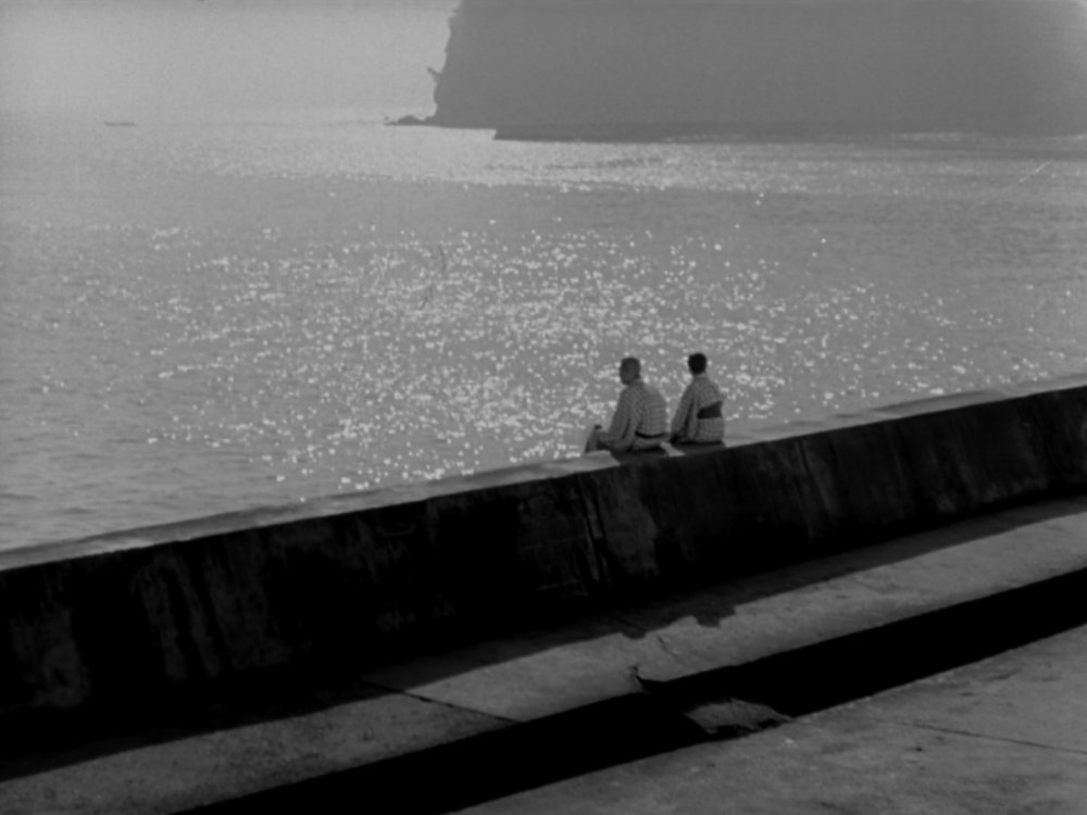 Shukichi and Tomi Hirayama (played by Chishu Ryu and Chieko Higashiyama) gaze out to sea from Atami, Japan in Yasujiro Ozu's film Tokyo Story (1953)