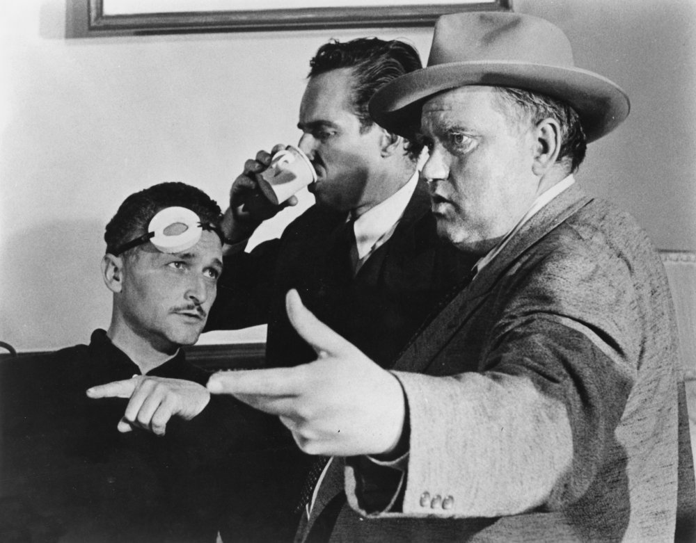Charlton Heston keeps himself caffeinated, while director of photography Russell Metty and Welles discuss a shot