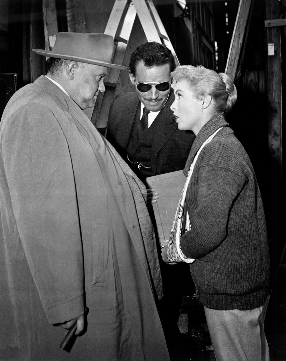 Janet Leigh, with her arm in a sling, talks with Welles and Heston. Leigh broke her arm a week before rehearsals started for the film and had to conceal the cast throughout much of filming