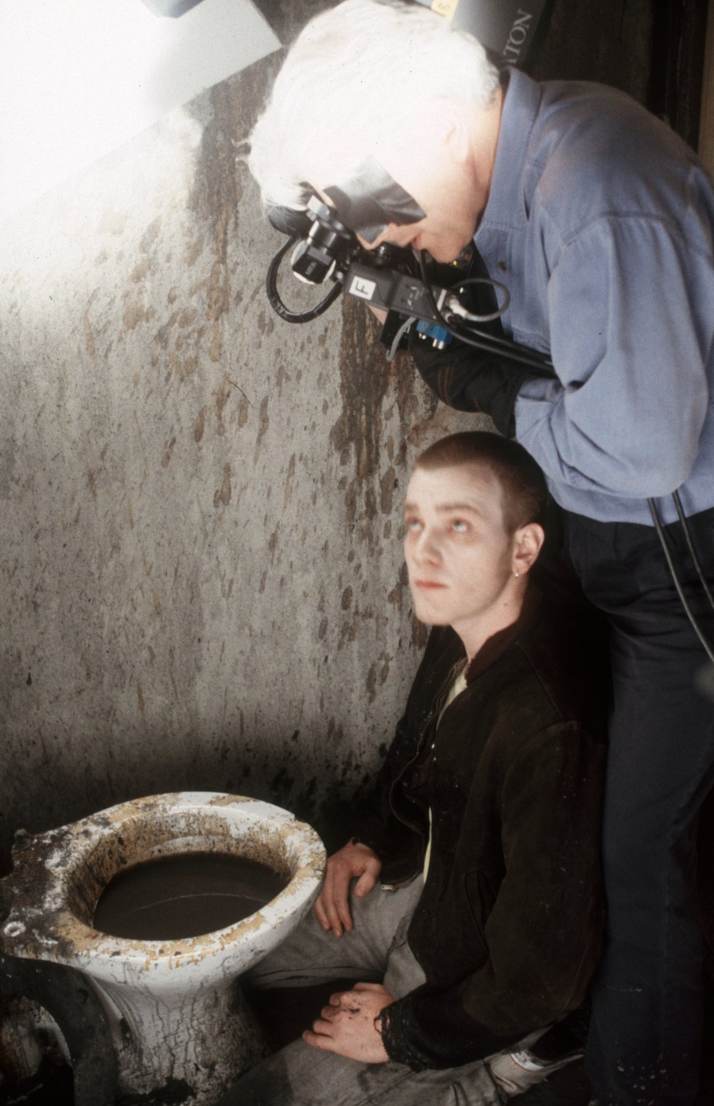 Cinematographer Brian Tufano lines up a shot for the infamous toilet diving sequence with Ewan McGregor