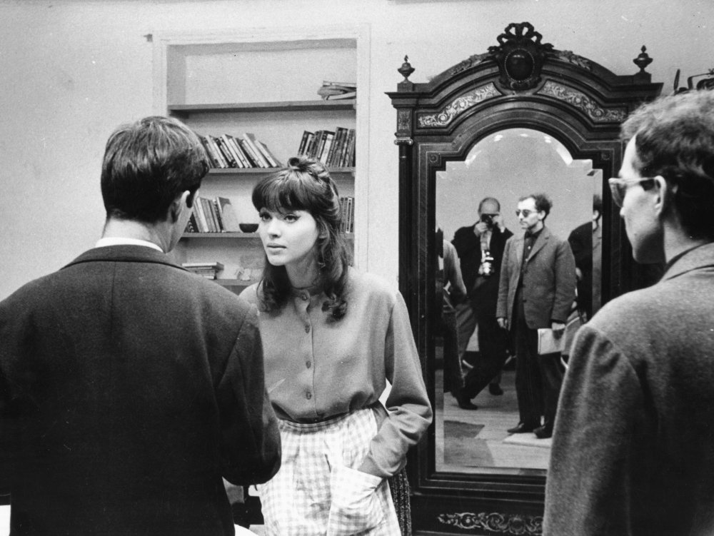 Godard (reflected in the mirror) preparing a scene with his then-wife Anna Karina for his 1961 film Une femme est une femme, a playfully experimental tribute to the Hollywood musical