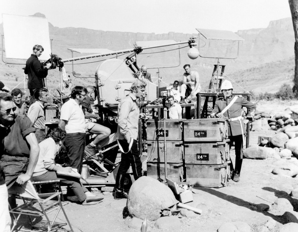 Michael Caine enjoys a moment out of full costume, as the lighting crew prepare the next shot on location for Zulu (1964). Top-billed Stanley Baker (right), meanwhile, is top-to-toe in helmet and bright red uniform.
