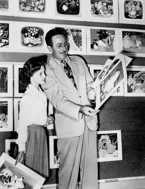 Walt Disney shows actor Kathryn Beaumont the storyboards for Alice in Wonderland (1951)