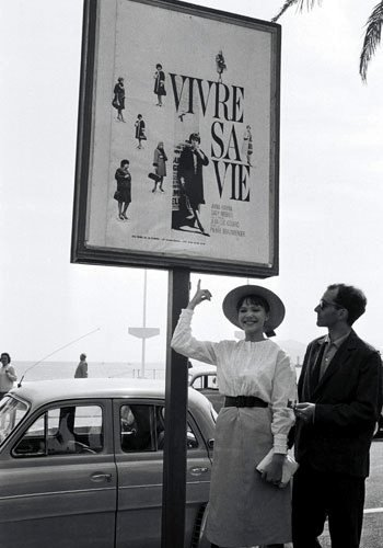 Anna Karina and Jean-Luc Godard on the Croisette underneath a poster for their film Vivre sa vie